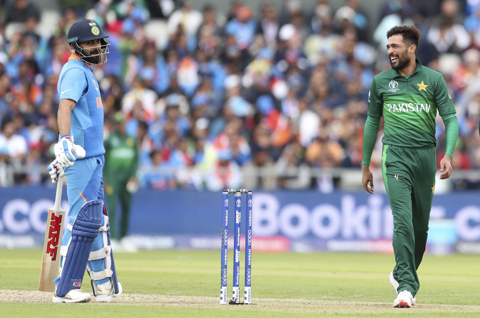 Pakistan's Mohammad Amir (R) talks to India's captain Virat Kohli (L) during a Cricket World Cup match at Old Trafford, Manchester, England, June 16, 2019. (AP Photo)