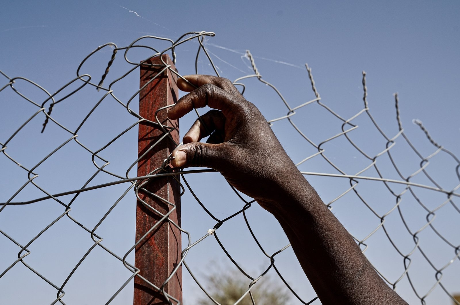 The hand and arm of a refugee on the perimeter fence of Tillaberi Refugee settlement located some 50 miles (80 kilometers) from Niger's capital of Niamey, Dec. 13, 2019. (Getty Images Photo)