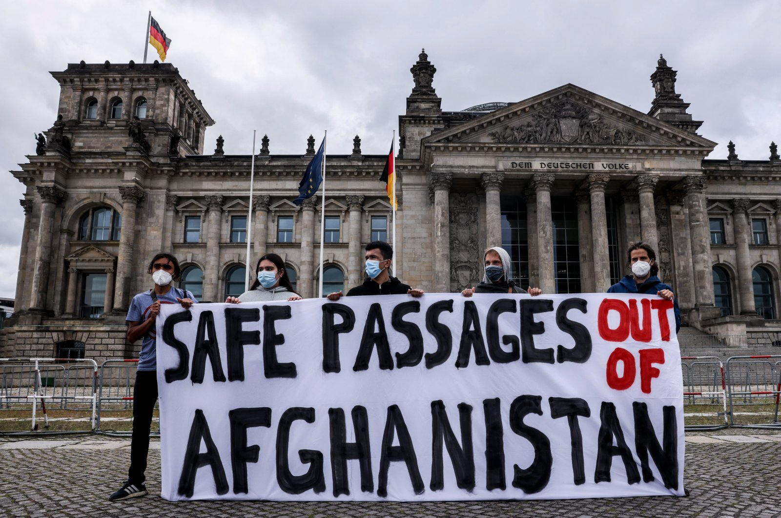 People shows banner during a protest called Air Bridge from Afghanistan in front of the German parliament 'Bundestag'  in Berlin, Germany, 17 August 2021. (EPA Photo)