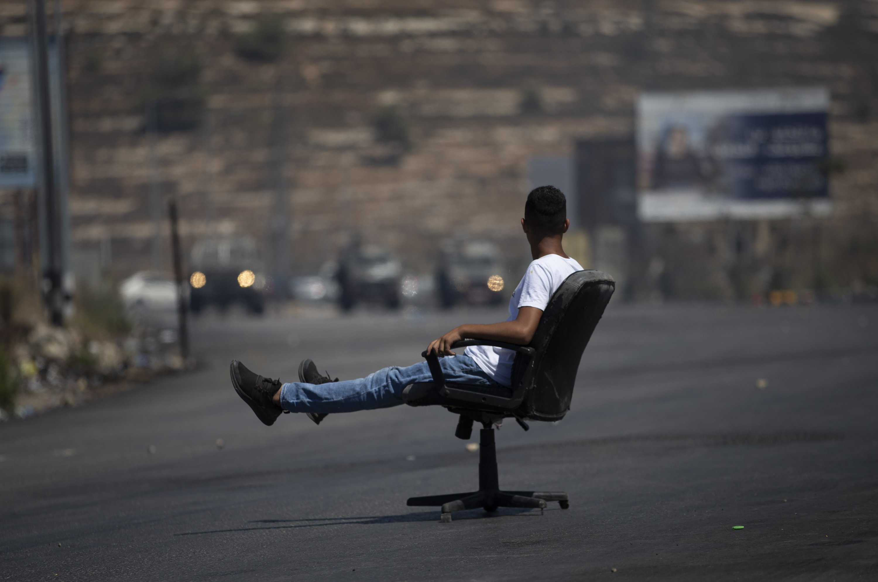 A Palestinian protester sits in a chair during clashes with Israeli forces over the killing of four Palestinians in the Jenin refugee camp by Israeli forces at the northern entrance of the West Bank city of Ramallah, Palestine, Aug. 17, 2021. (AP Photo)