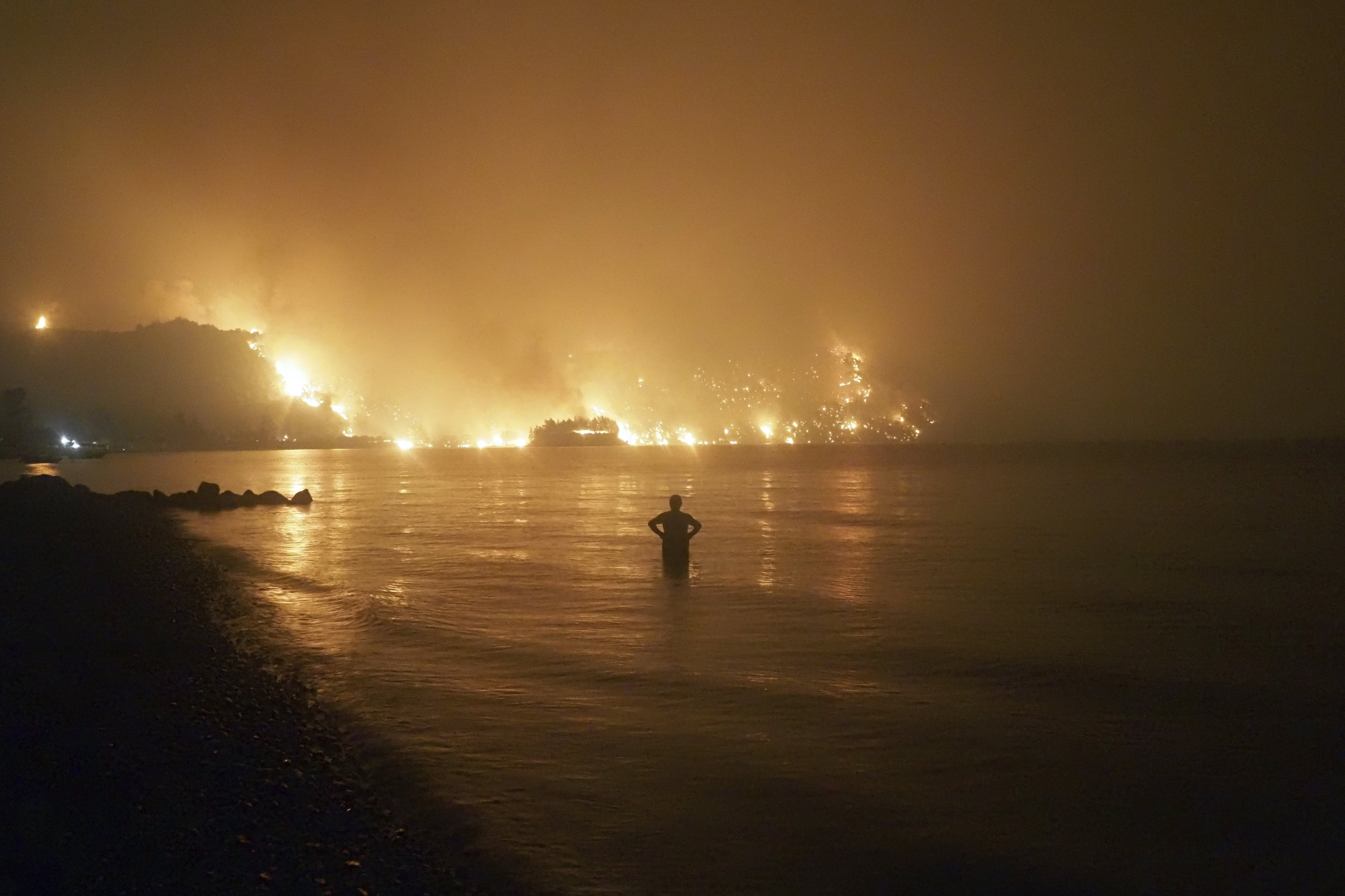 A man watches the flames as a wildfire approaches Kochyli beach near Limni village on the island of Evia, about 160 kilometers (100 miles) north of Athens, Greece, Aug. 6, 2021. (AP Photo)