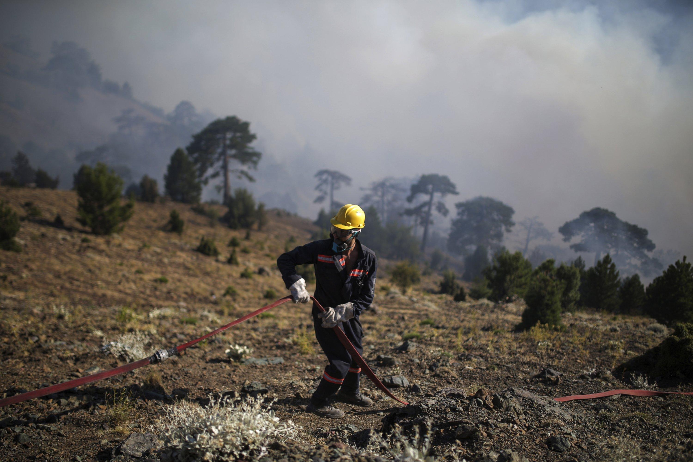 A firefighter adjusts a hosepipe as they extinguish a wildfire in Koycegiz, Mugla, Turkey, Monday, Aug. 9, 2021. (AP Photo)