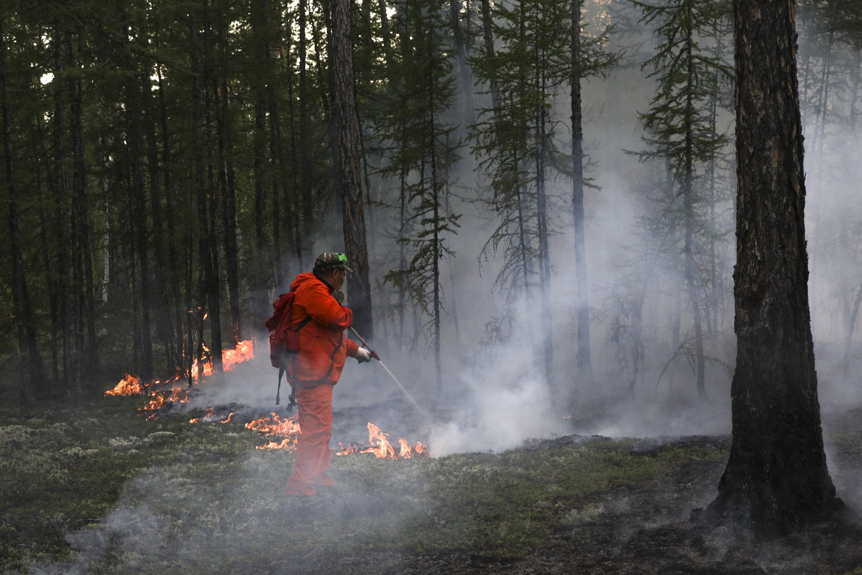 Firefighters and volunteers work at the scene of a forest fire near Magan village in Yakutsk region, republic of Sakha, far east Russia, Aug. 10, 2021. (AP Photo)