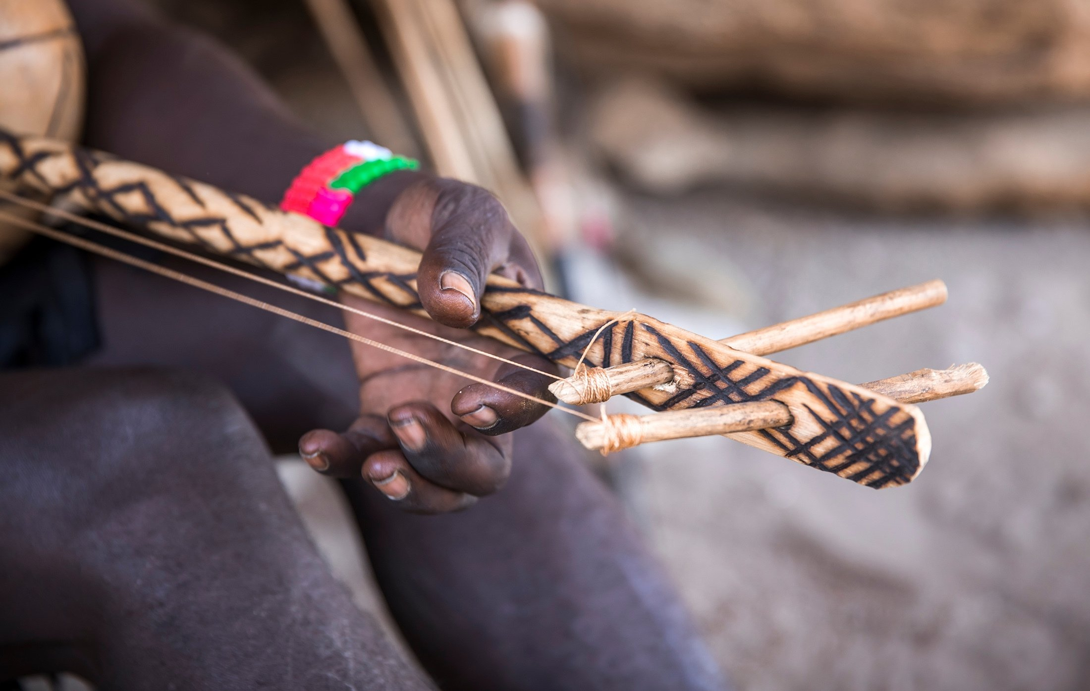A Hadza man plays a homemade musical instrument in Tanzania. (Shutterstock Photo)