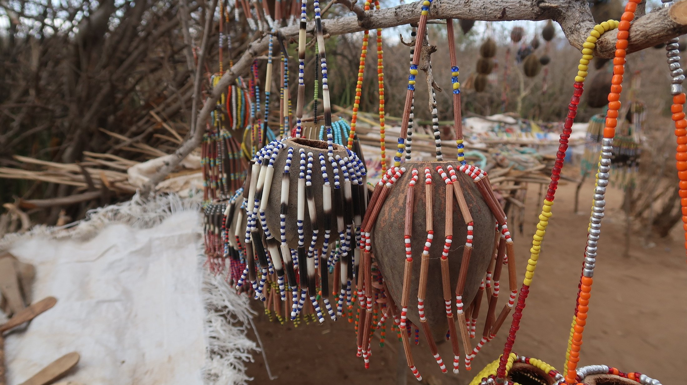Souvenirs made by the Hadza people hang from a bush in Tanzania. (Shutterstock Photo)