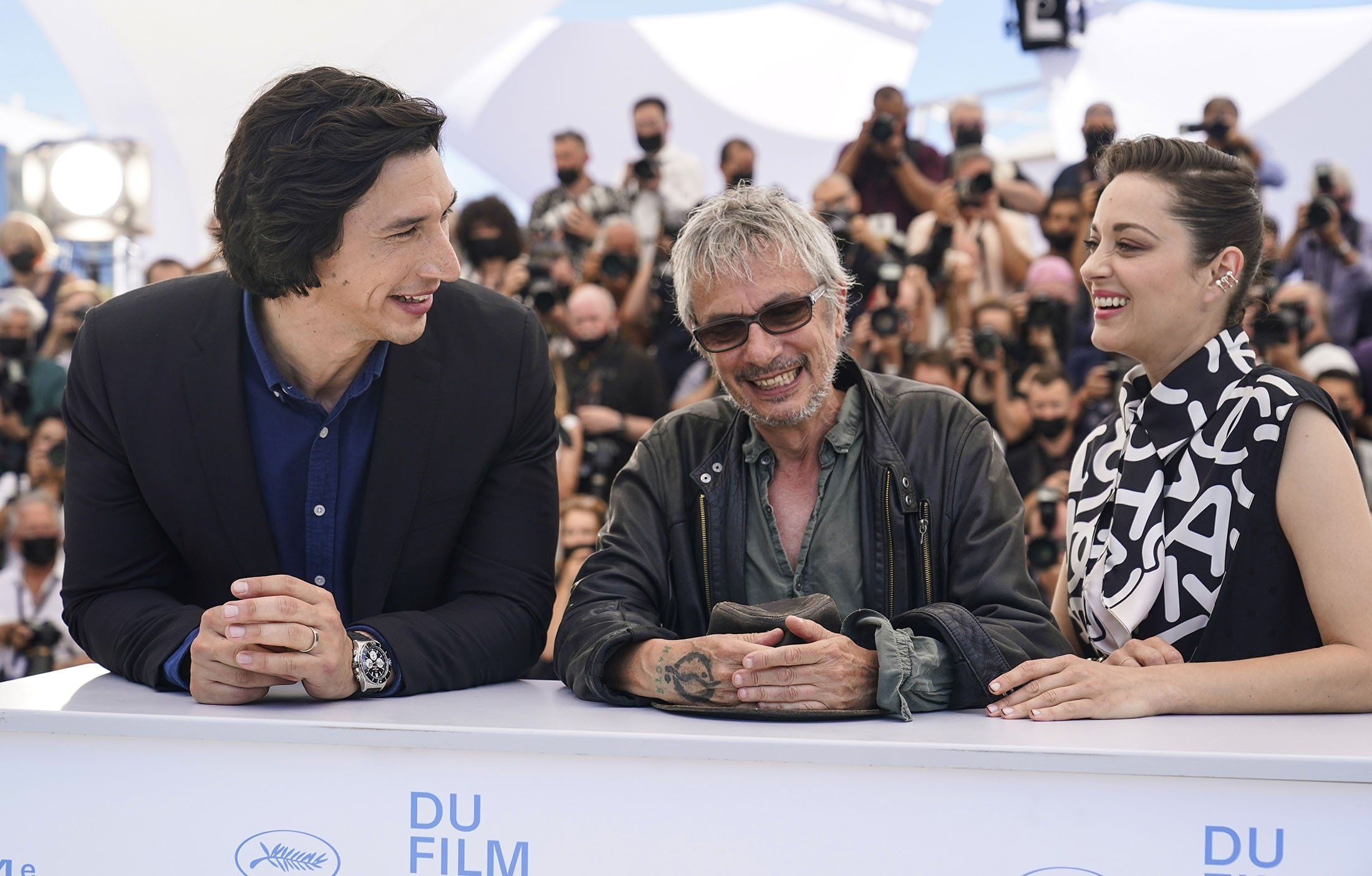 Actors Adam Driver (L) and Marion Cotillard appear with director Leos Carax at the photocall for their film 'Annette' at the 74th international film festival, Cannes, southern France, July 6, 2021. (AP Photo)
