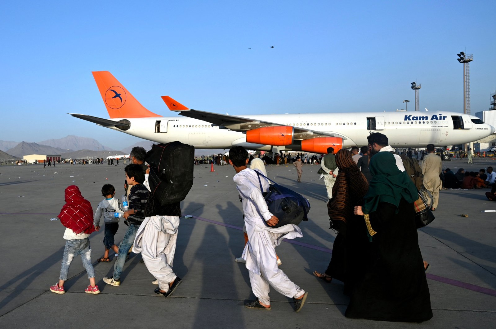 Afghan families walk by the aircraft at the Kabul airport in Kabul, Afghanistan, Aug.16, 2021. (AFP Photo)
