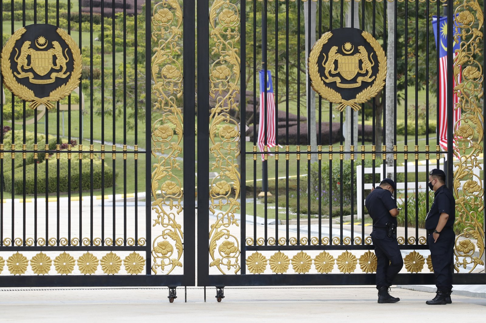 Police stand guard outside the main gate of the National Palace while Malaysia's Prime Minister Muhyiddin Yassin meets the king in Kuala Lumpur, Malaysia, Aug. 16, 2021. (AP Photo)