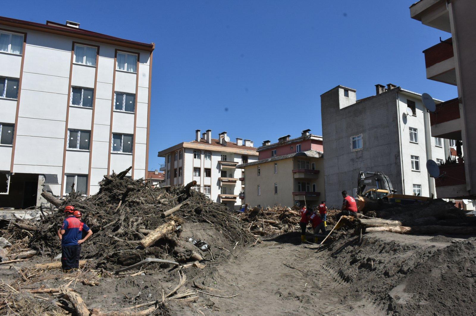 Workers clean the debris from the streets in flood-hit Bozkurt, Kastamonu, northern Turkey, Aug. 17, 2021. (AA PHOTO)