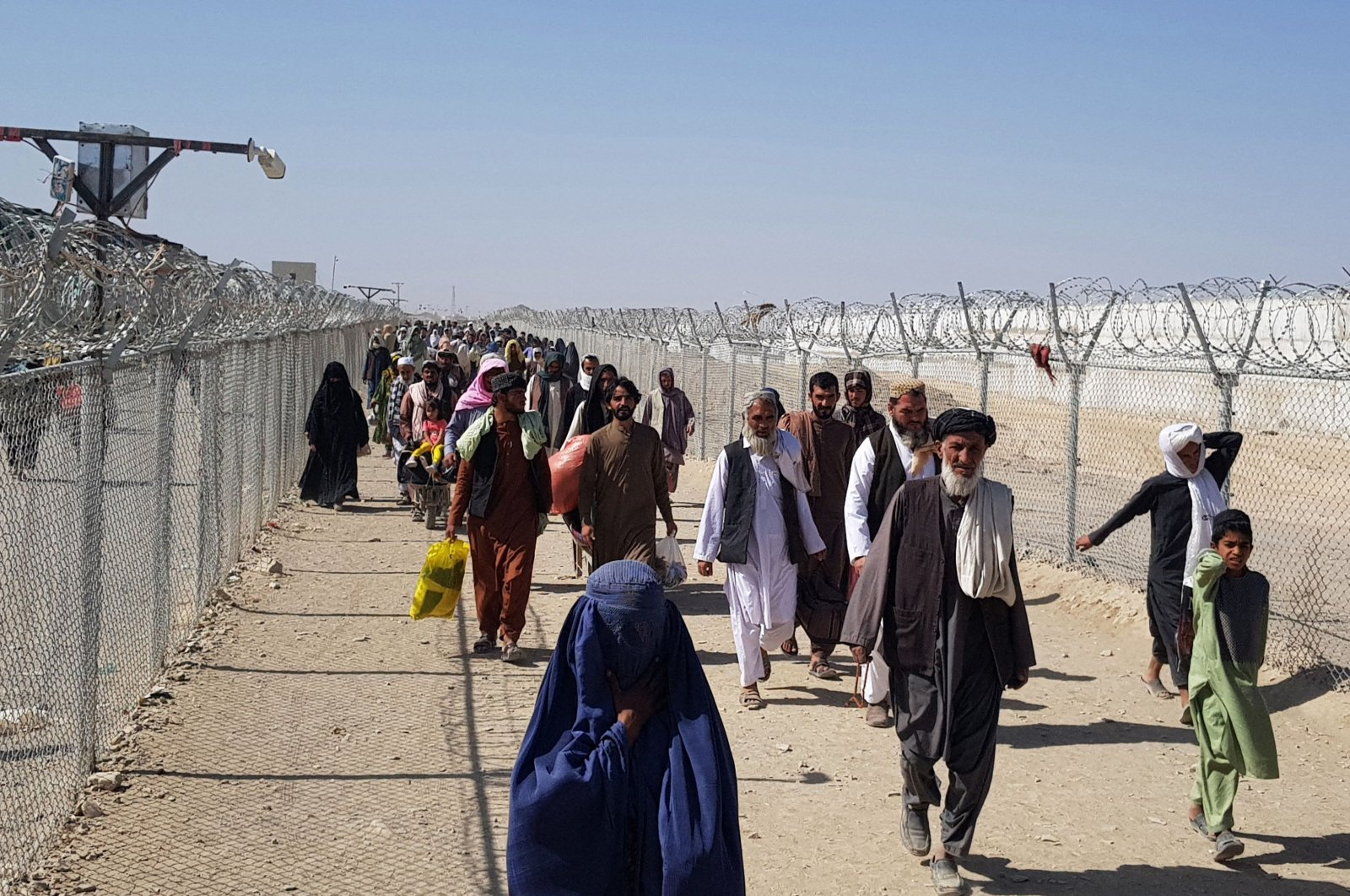 Afghan nationals cross the border into Pakistan at the Pakistan-Afghanistan border crossing in Chaman, Aug.18, 2021. (AFP Photo)