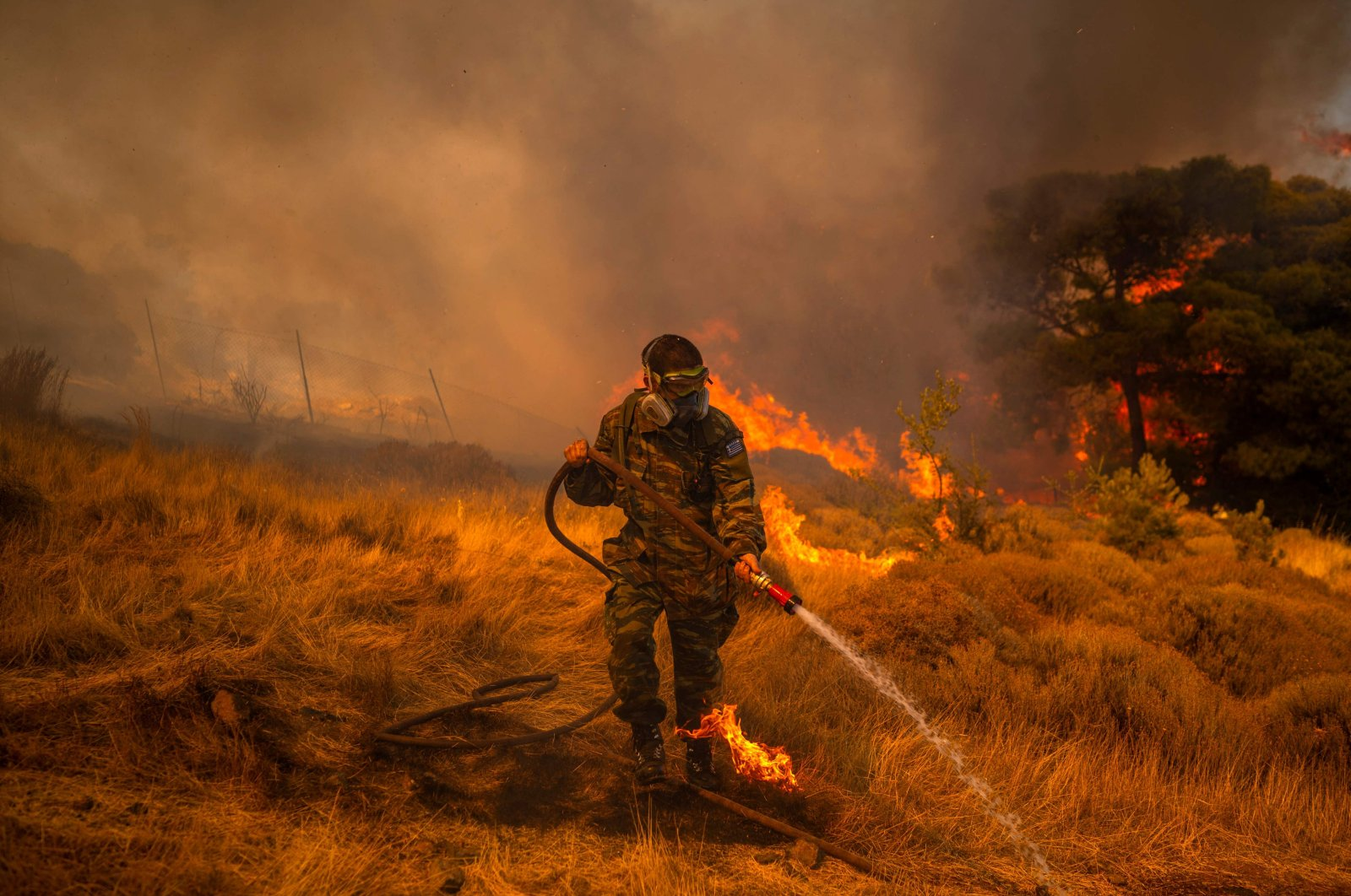 A volunteer uses a water hose to extinguish a fire in the village of Markati, near Athens, Greece, on Aug. 16, 2021. (AFP Photo)