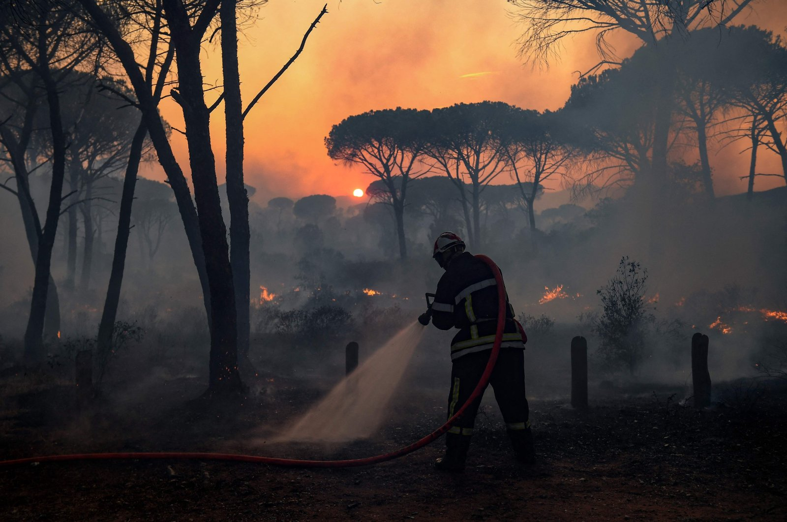 A French firefighter uses a water hose as light from the setting sun is filtered through smoke during a forest wildfire, near Gonfaron, in Var Prefecture, southern France, Aug. 17, 2021. (AFP Photo)