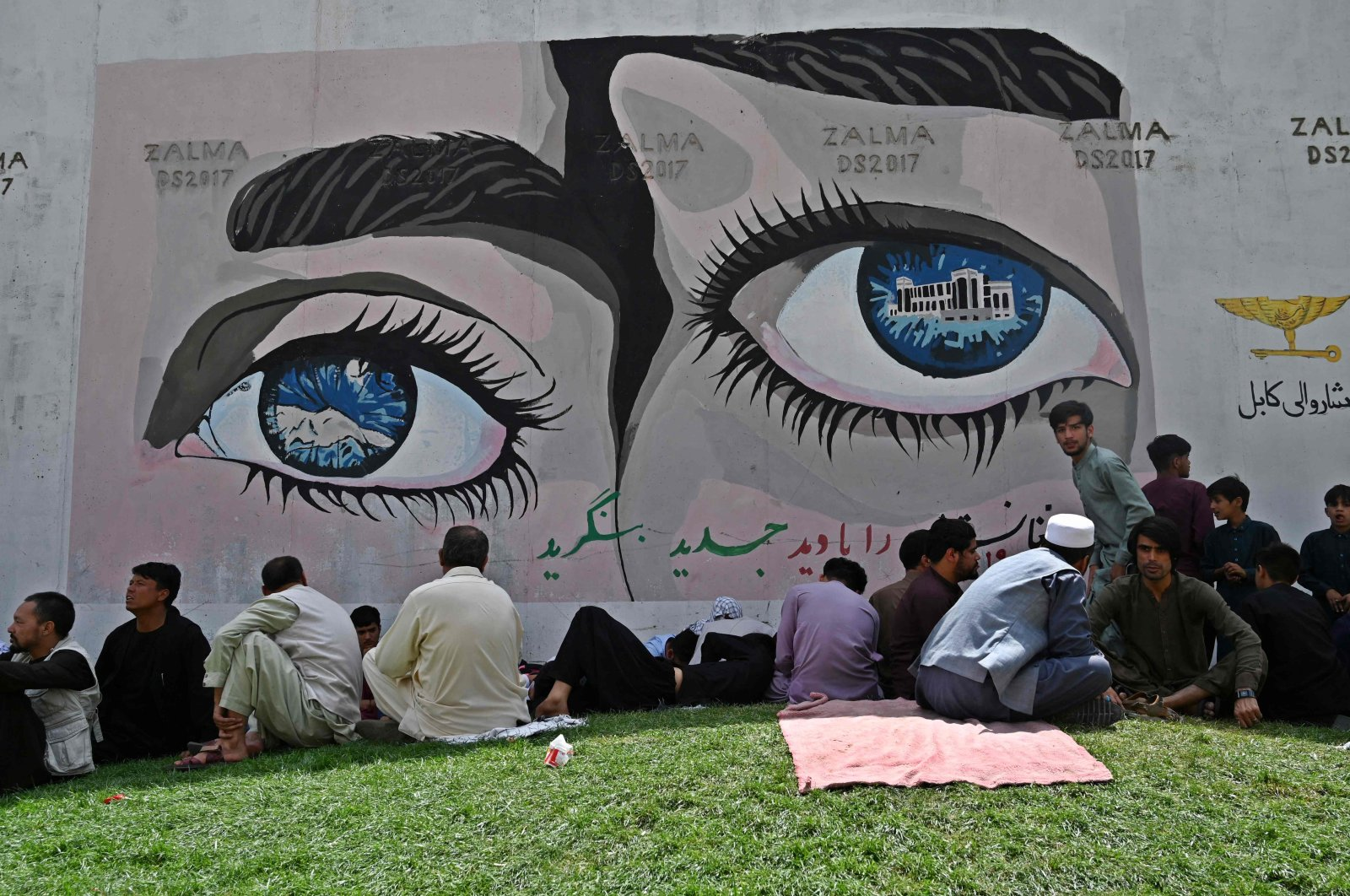People sit near the French Embassy following the Taliban's stunning takeover of Afghanistan, Kabul, Aug. 18, 2021. (AFP Photo)