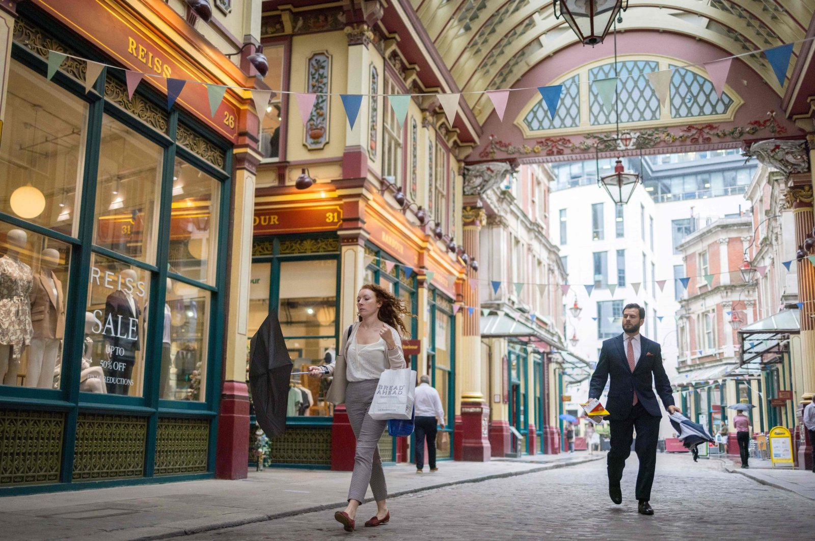 People walk past shops and restaurants at Leadenhall Market in the City of London, U.K., July 27, 2021. (AFP Photo)