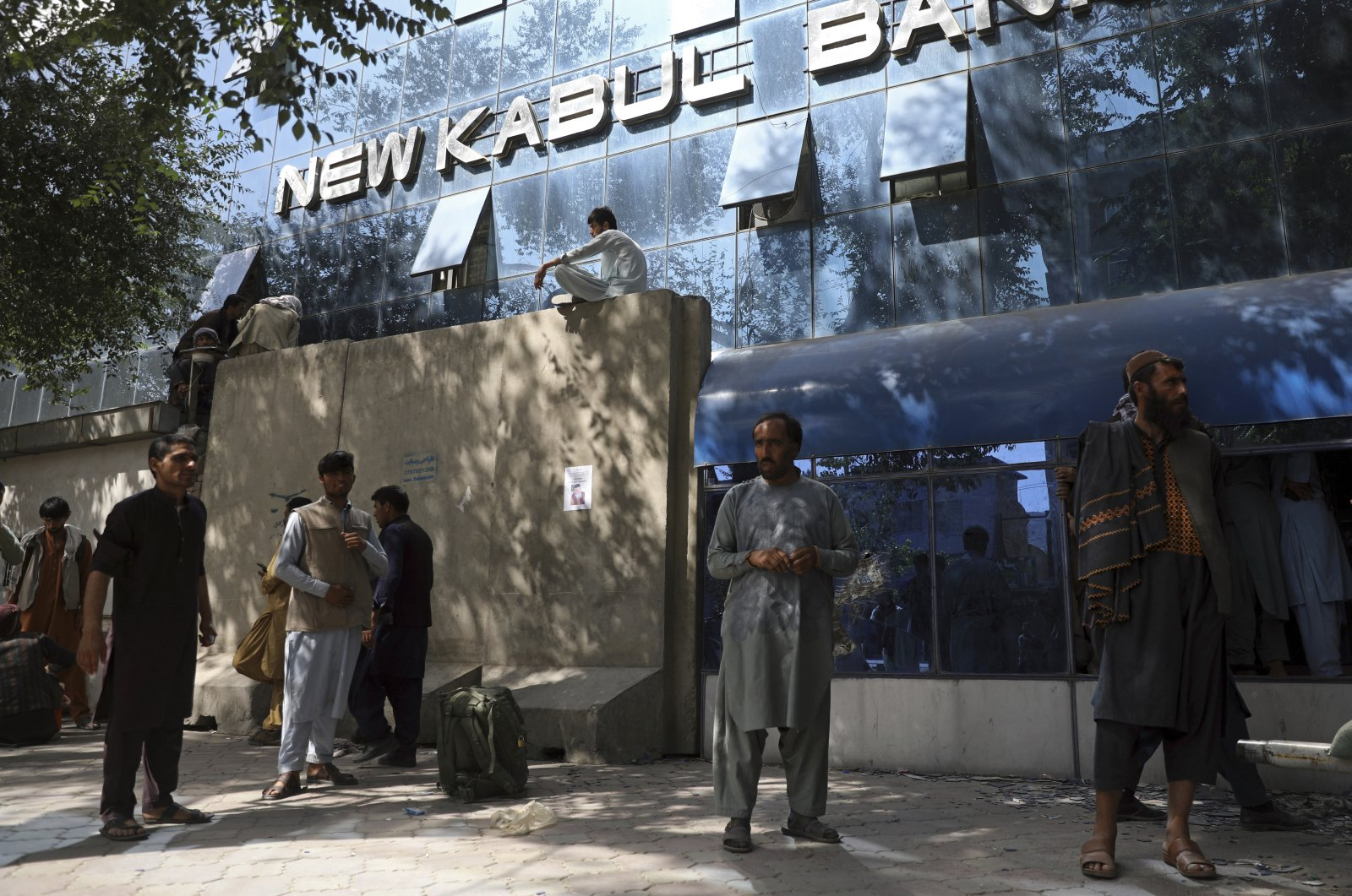 Afghans wait for hours to try to withdraw money, in front of New Kabul Bank, in Kabul, Afghanistan, Aug. 15, 2021. (AP Photo)