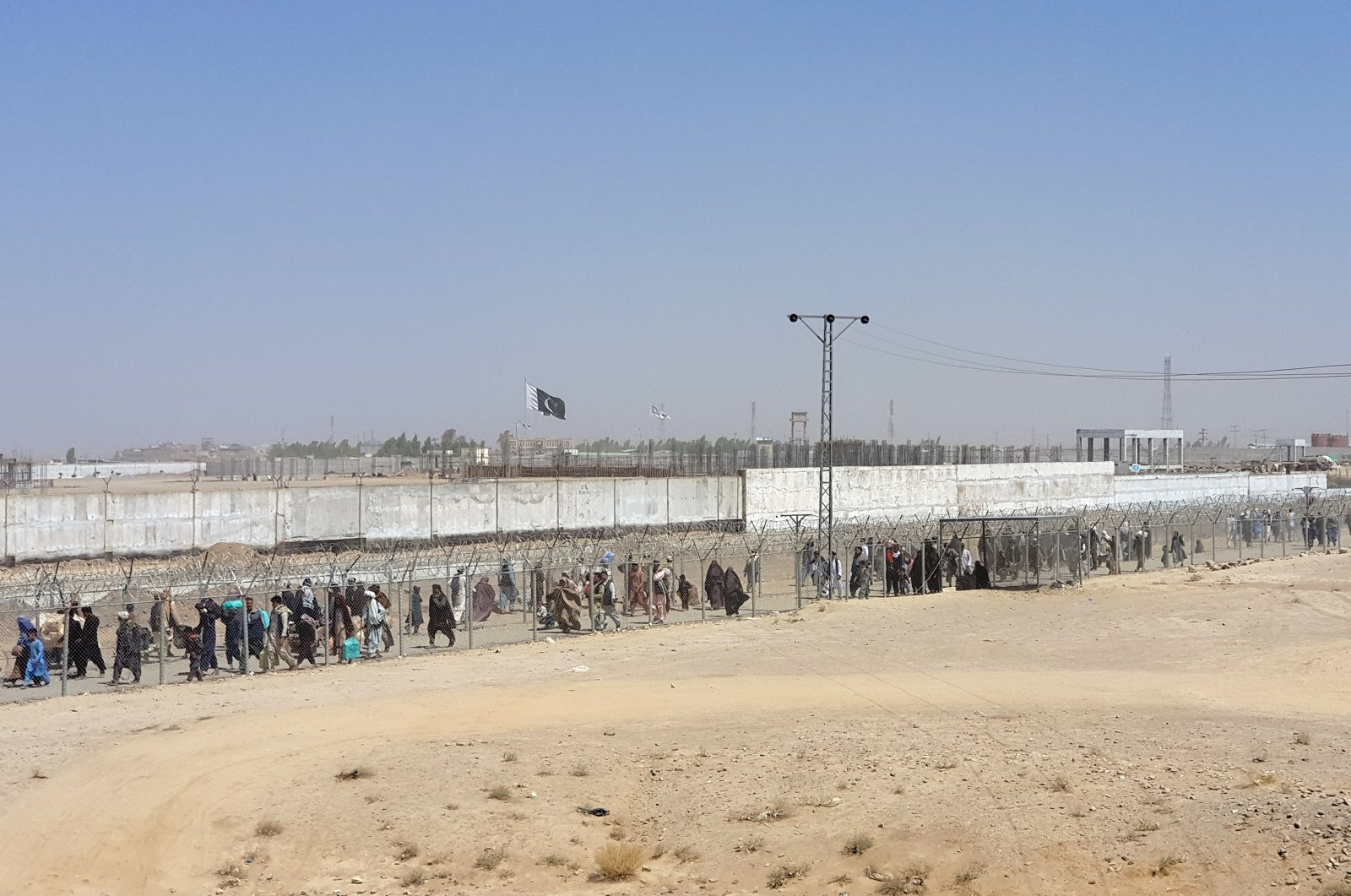People arriving from Afghanistan cross the fence at the Friendship Gate crossing point, in the Pakistan-Afghanistan border town of Chaman, Pakistan, Aug. 18, 2021. (REUTERS)