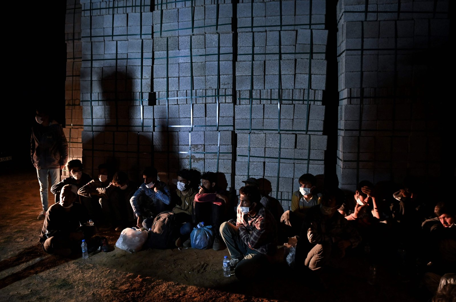 Afghan migrants rest while they wait for transport by smugglers after crossing the Iran-Turkish border on August 15, 2021 in Tatvan, on the western shores of Lake Van, eastern Turkey. (Photo by Ozan KOSE / AFP)