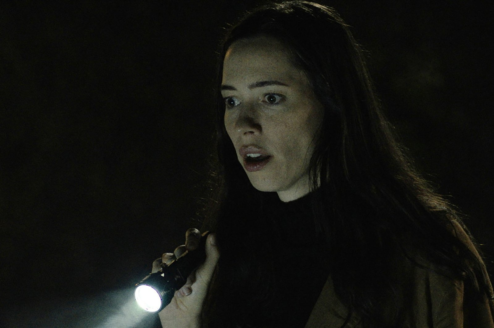 """Rebecca Hall holds a flashlight, in a scene from the film """"The Night House.""""(Searchlight Pictures via AP)"""