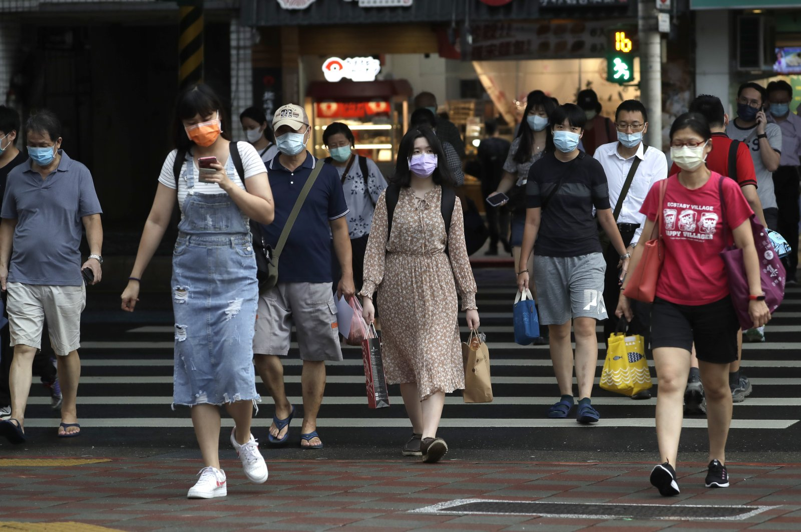 People wear face masks to help protect against the spread of the coronavirus in Taipei, Taiwan, Aug. 11, 2021. (AP Photo)