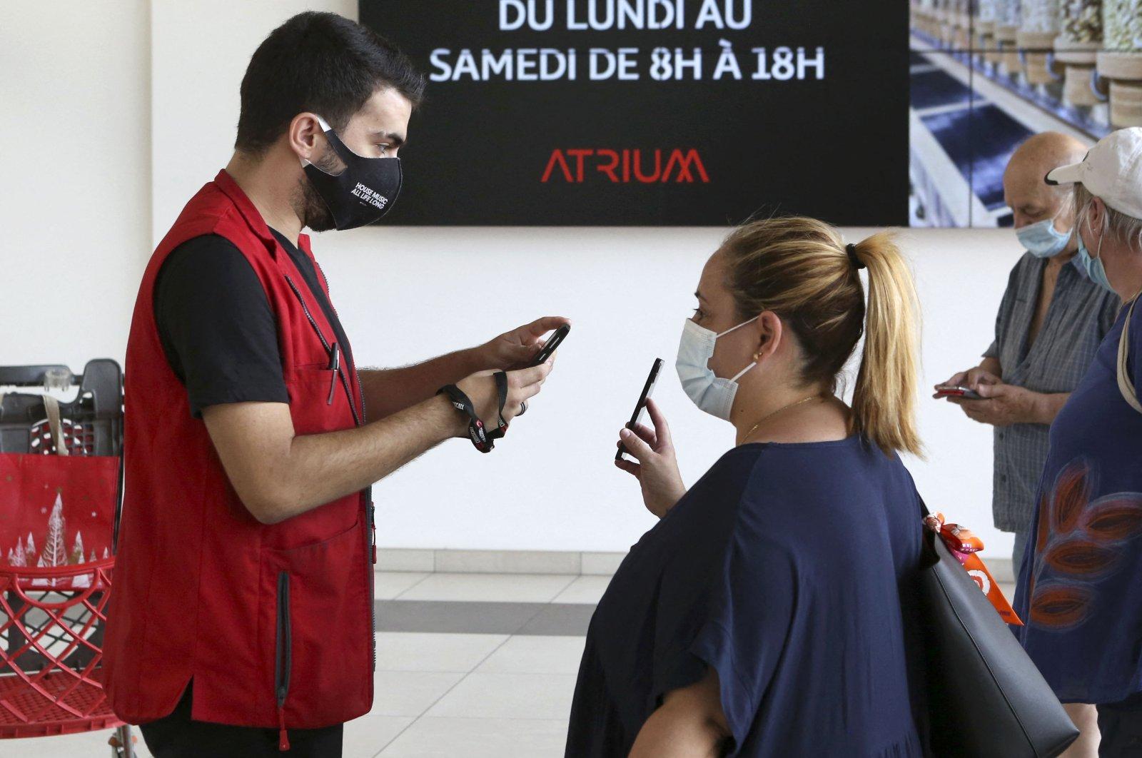 An employee of the Atrium shopping center checks a visitor's health pass in Ajaccio, South Corsica, Aug. 16, 2021. (AFP Photo)