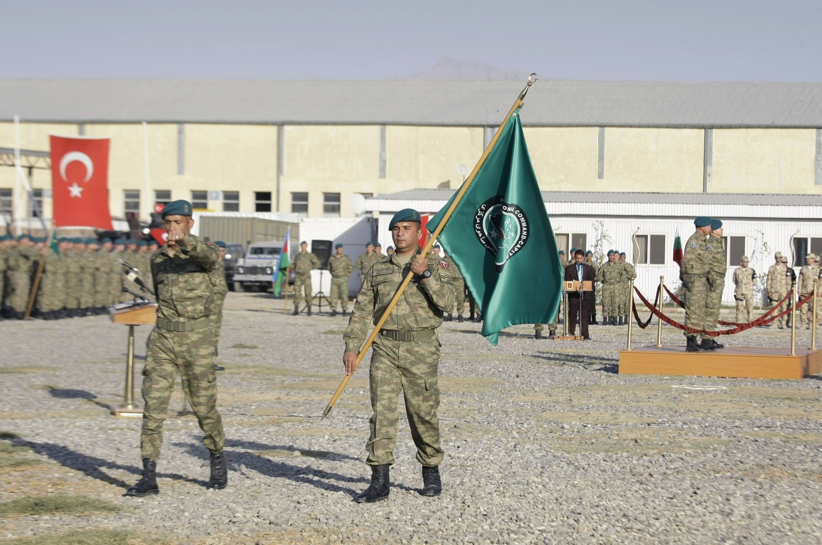 A Turkish soldier, part of the NATO forces, carries a flag of the Regional Command Capital during a change of command ceremony at NATO's Turkish run camp Dogan in Kabul, Afghanistan, Oct. 29, 2012. (AP File Photo)
