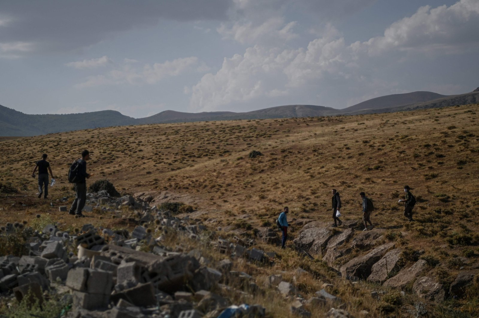 Afghan migrants walk while waiting for transport by smugglers after crossing the Iran-Turkish border in Tatvan on the western shores of Lake Van, eastern Turkey, Aug. 15, 2021 (AFP Photo)