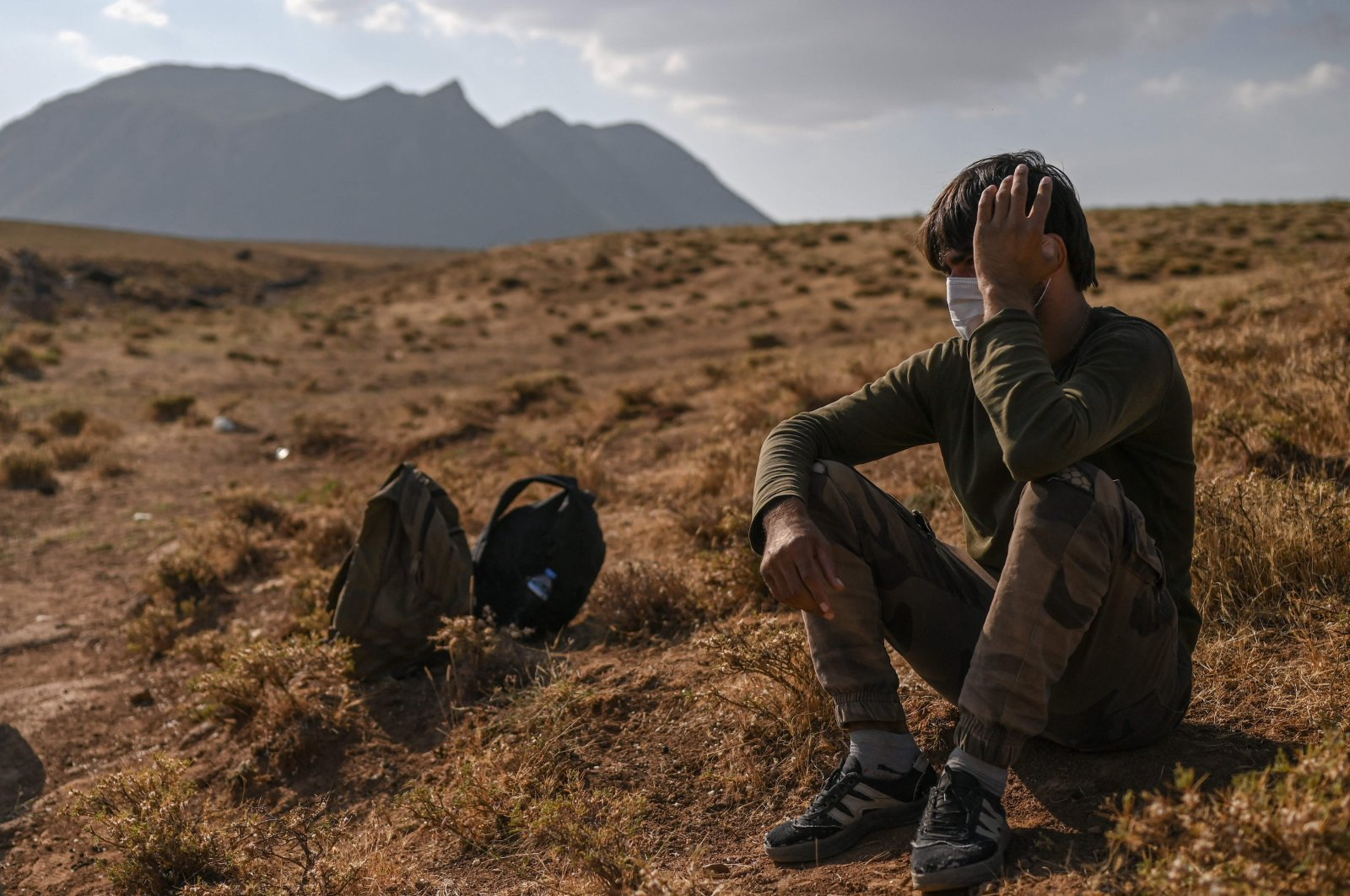 An Afghan migrant rests while waiting for transport by smugglers after crossing the Iran-Turkish border on Aug. 15, 2021, in Tatvan, on the western shores of Lake Van, eastern Turkey. (AFP Photo)