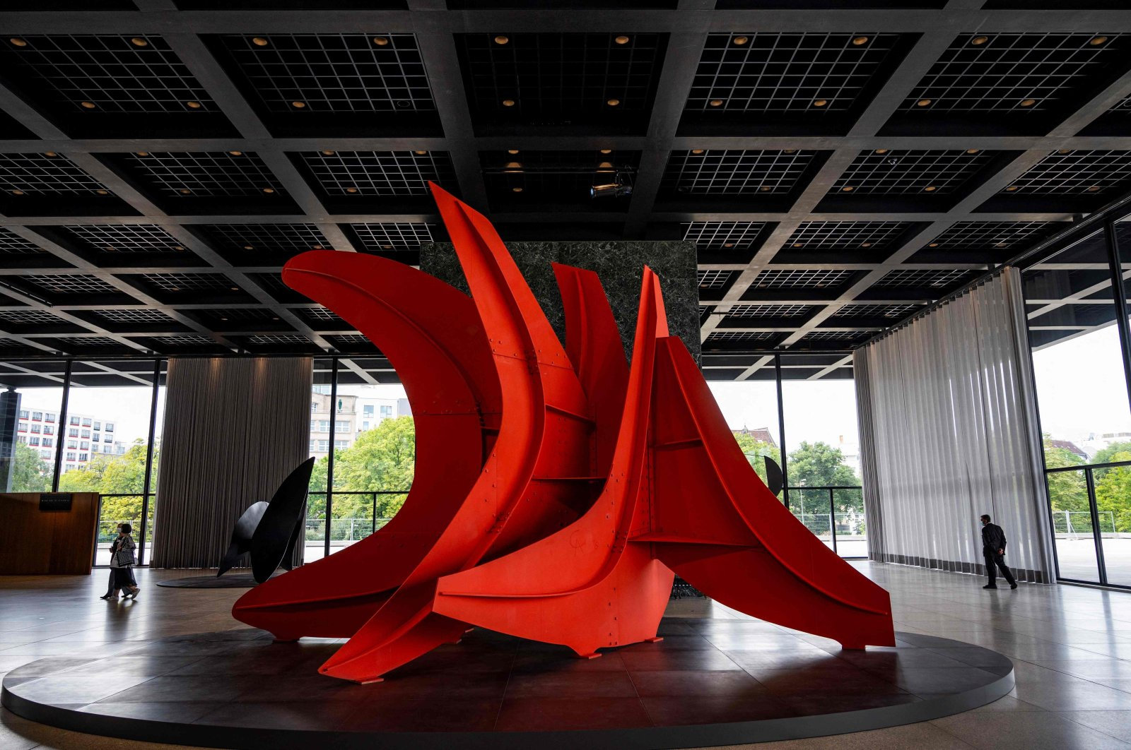 """Visitors walk past U.S. sculptor Alexander Calder's work """"Five Swords"""" during a press preview of the exhibition """"Alexander Calder Minimal/Maximal"""" at the Neue Nationalgalerie (New National Gallery) museum, on Aug. 18, 2021, in Berlin. (AFP Photo)"""