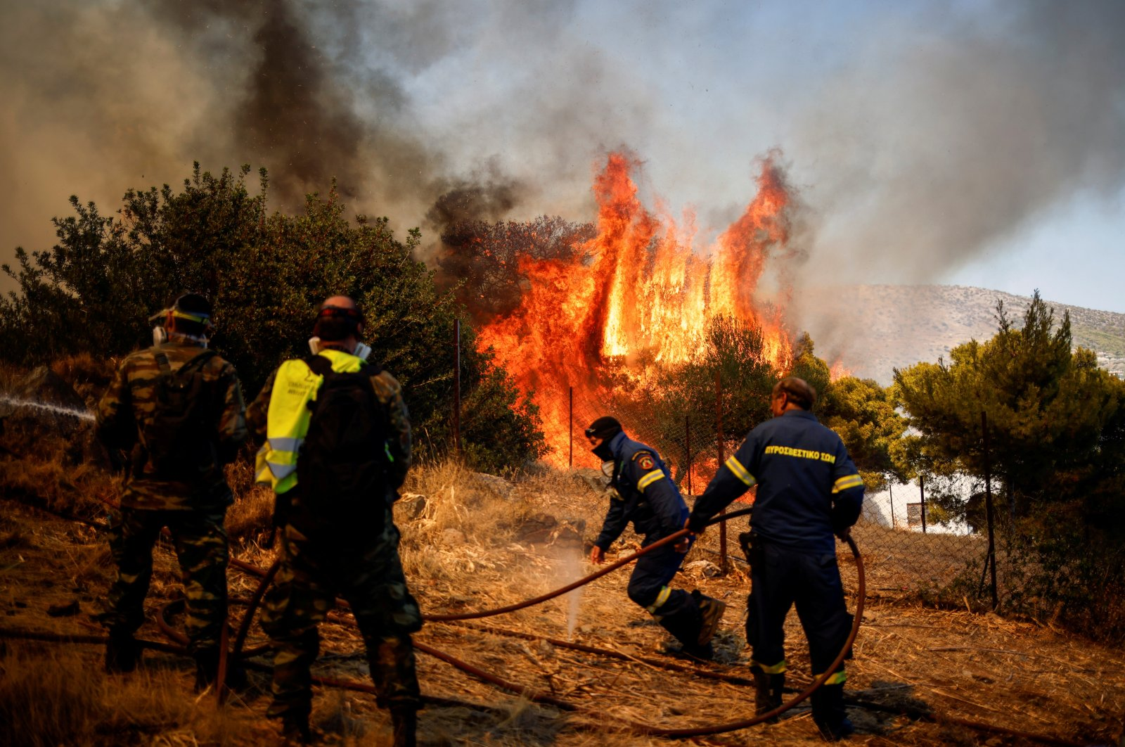Firefighters and volunteers try to extinguish a wildfire burning in the village of Markati, near Athens, Greece, Aug. 16, 2021. (Reuters Photo)
