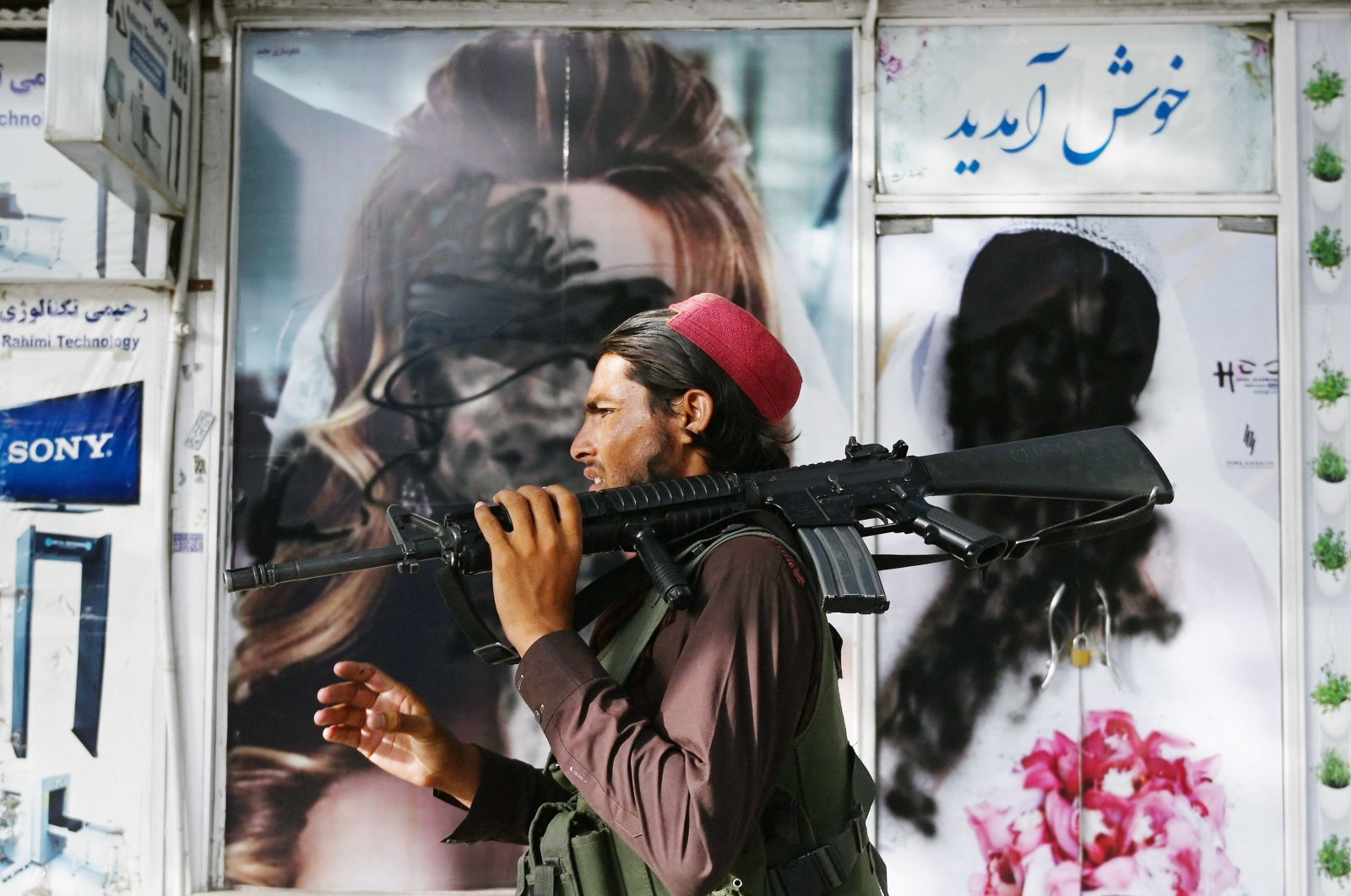 A Taliban fighter walks past a beauty salon with images of women defaced using spray paint in Shar-e-Naw in Kabul, Afghanistan, on Aug. 18, 2021. (AFP Photo)