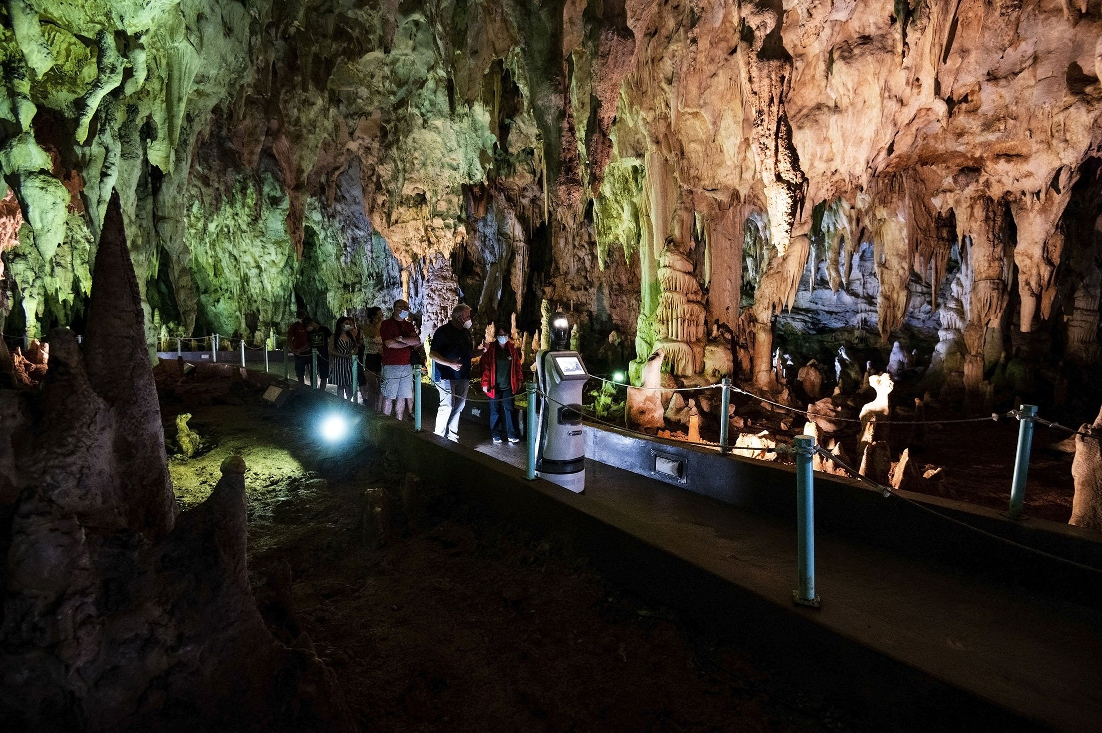 Persephone guides the visitors inside Alistrati cave, about 135 kilometers (84 miles) northeast of Thessaloniki, Greece, Aug. 2, 2021. (AP Photo)