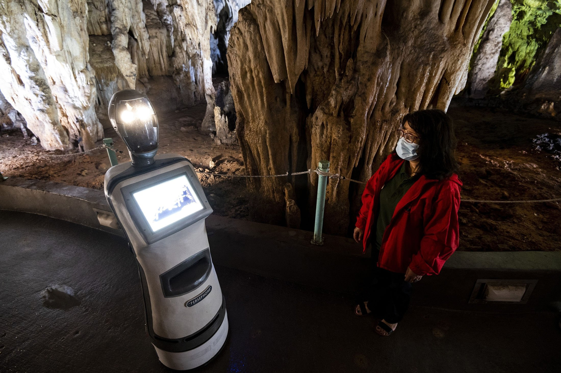 A guide programs Persephone inside Alistrati cave, about 135 kilometers (84 miles) northeast of Thessaloniki, Greece, Aug. 2, 2021. (AP Photo)