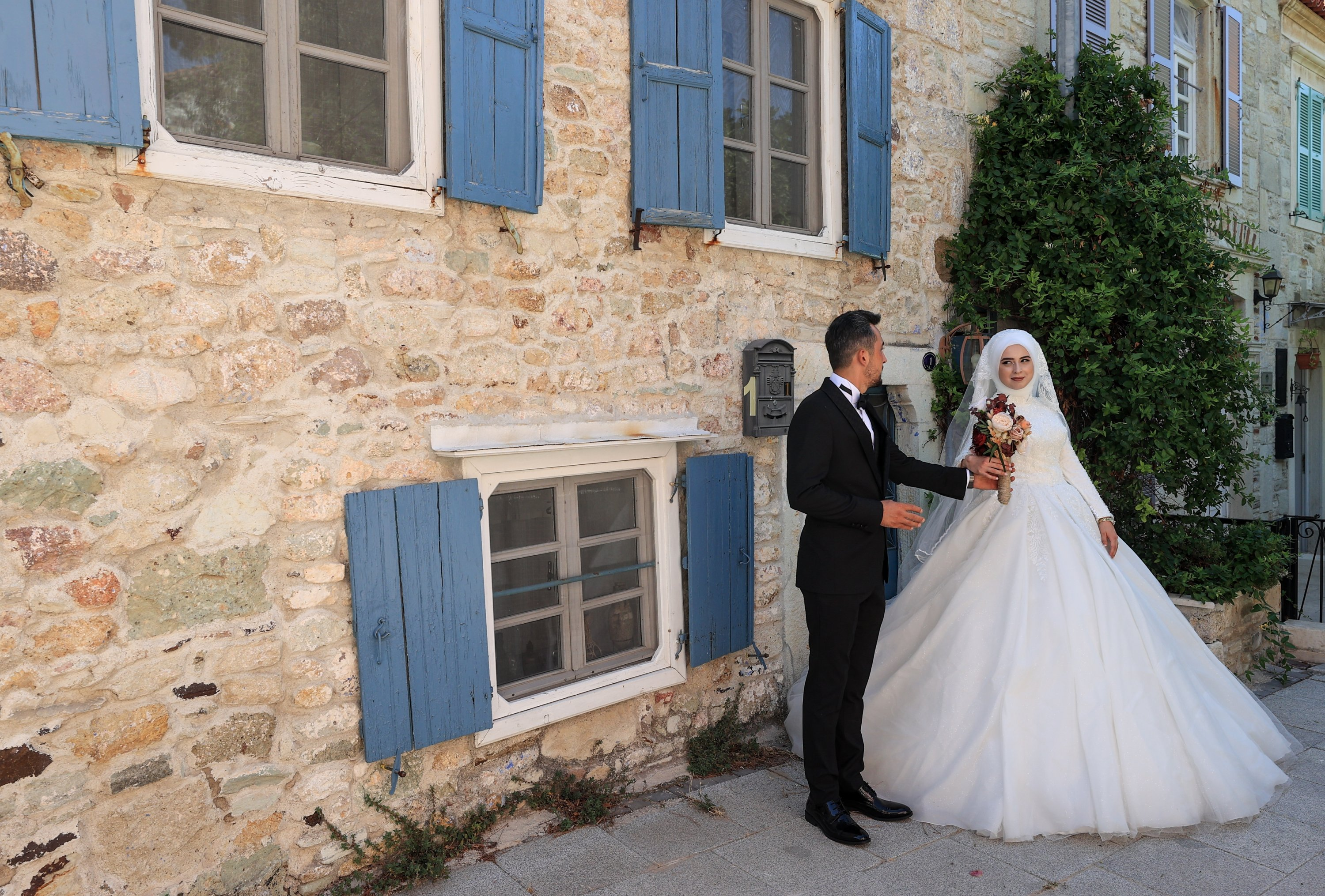 A bride and groom pose for their wedding photos in front of a stone house in Foça district, Izmir, western Turkey, Aug. 18, 2021. (AA Photo)