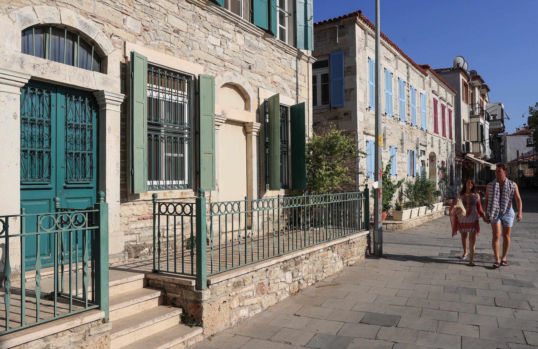 People walk by stone houses in Foça district, Izmir, western Turkey, Aug. 18, 2021. (AA Photo)
