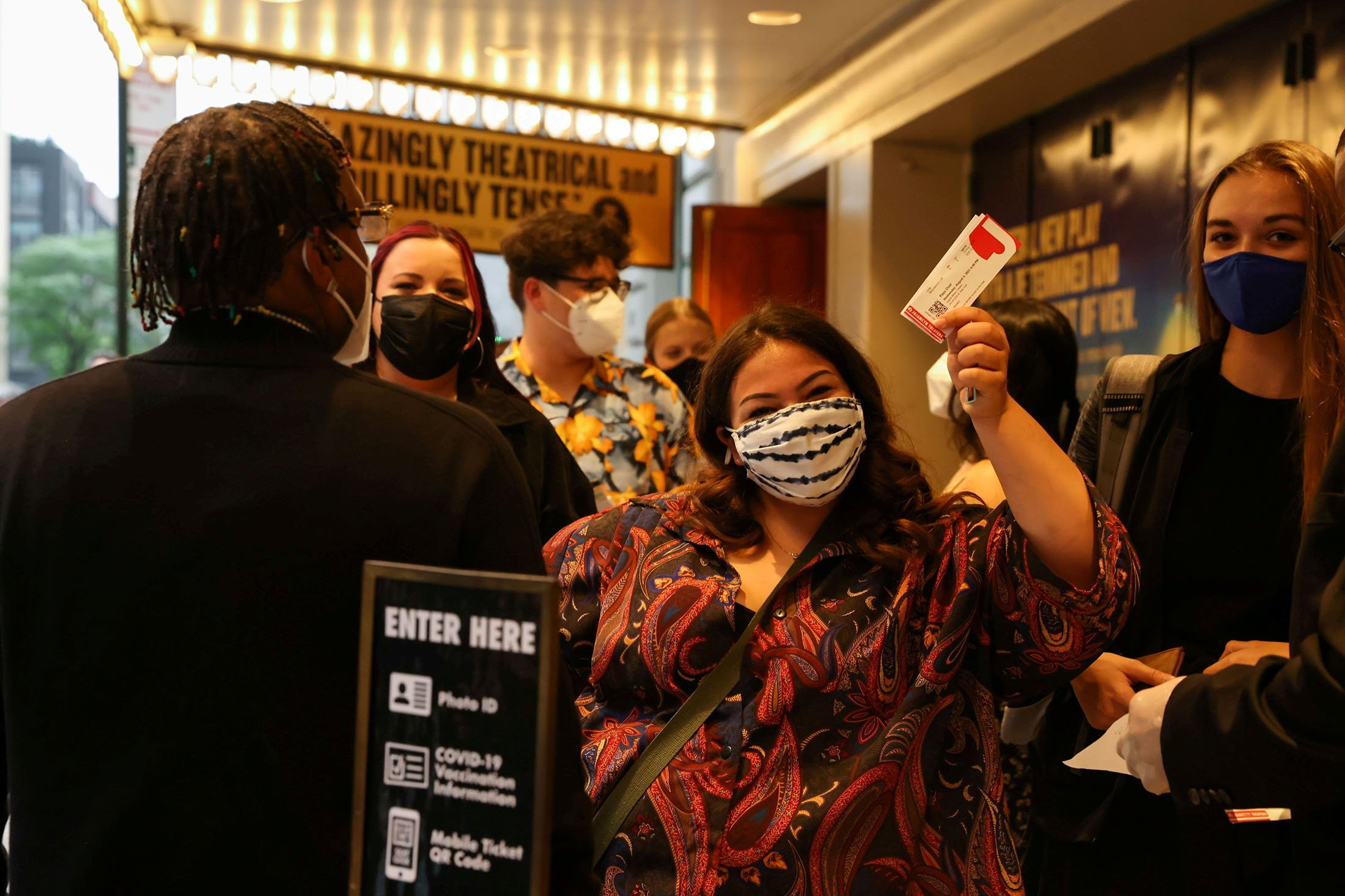 A guest waves her tickets while waiting in line at the opening night of previews for 'Pass Over,' following the 17-month shutdown of Broadway due to COVID-19, at the August Wilson Theater in New York City, U.S., Aug. 4, 2021. (Reuters Photo)