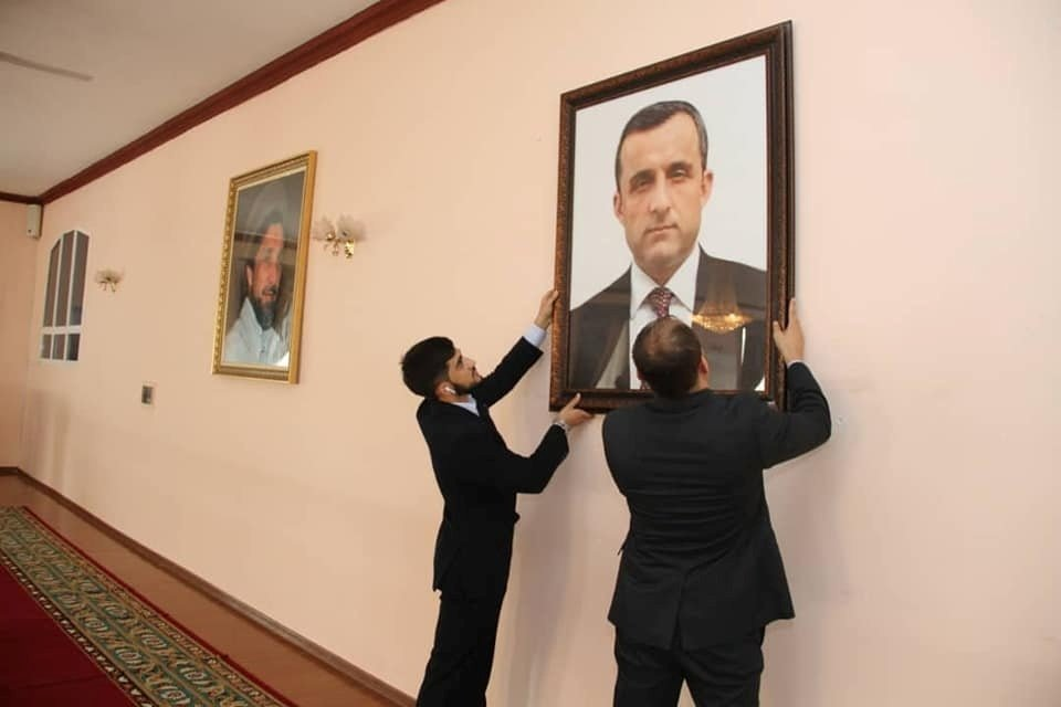 """Afghan embassy staff hang a portrait of Afghan Vice President Amrullah Saleh, who declared himself the """"legitimate caretaker president,"""" on the wall at the embassy in Dushanbe, Tajikistan, in this picture released August 18, 2021. (Embassy of the Islamic Republic of Afghanistan in Dushanbe via Reuters)"""