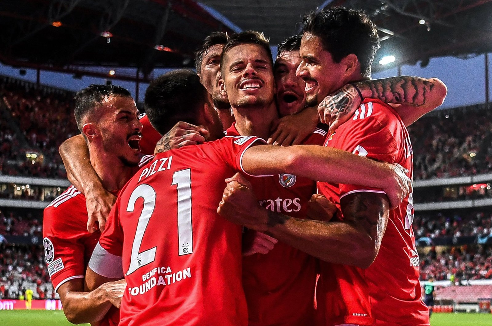 Benfica's German midfielder Julian Weigl (C) celebrates with teammates scoring his side's second goal during the UEFA Champions League play-off first leg match against PSV Eindhoven at the Luz stadium, Lisbon, Portugal, Aug. 18, 2021. (AFP Photo)