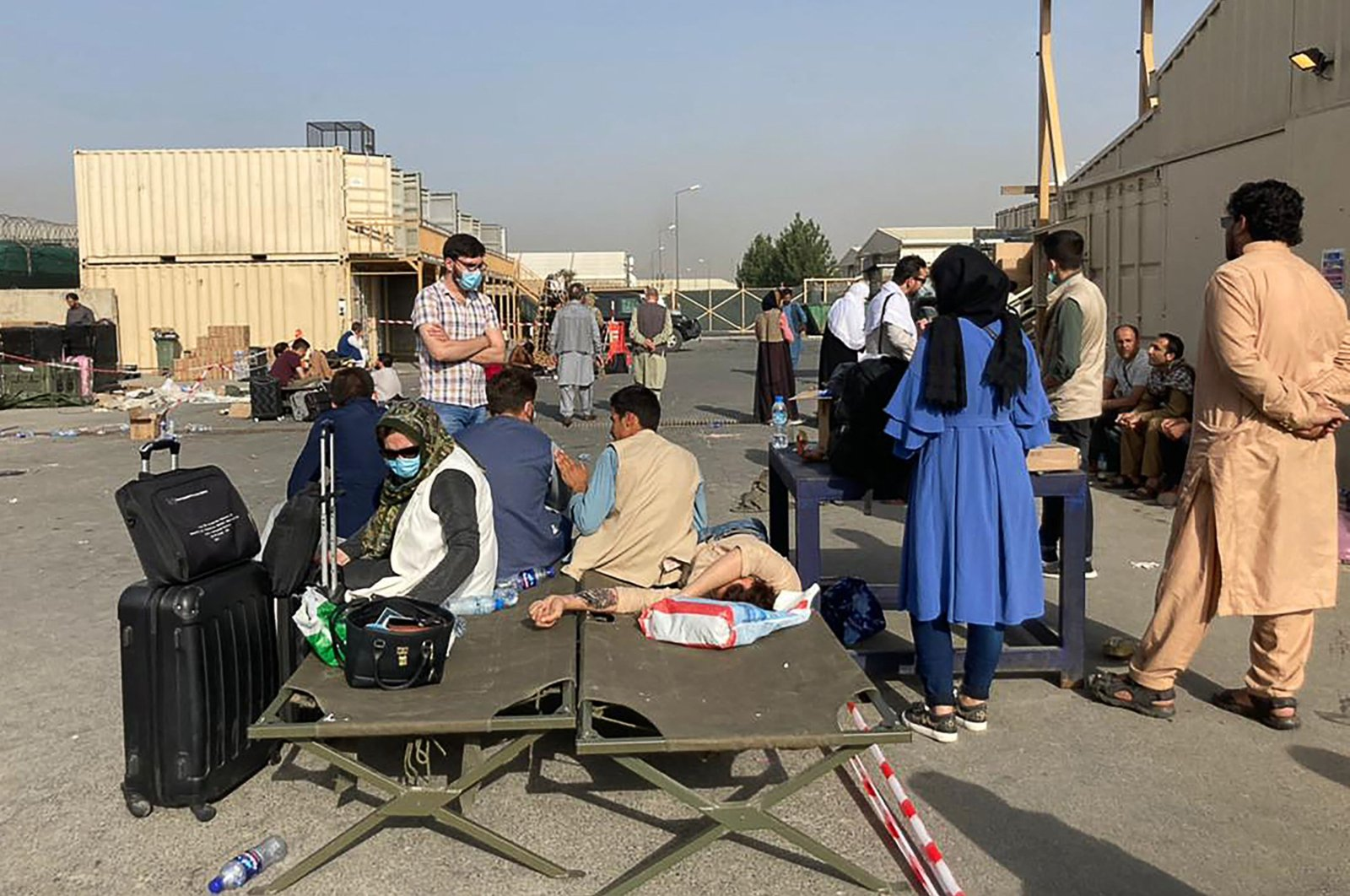 People wait to be evacuated from Afghanistan at the airport in Kabul on Aug. 18, 2021 following the stunning Taliban takeover of the country. (AFP Photo)
