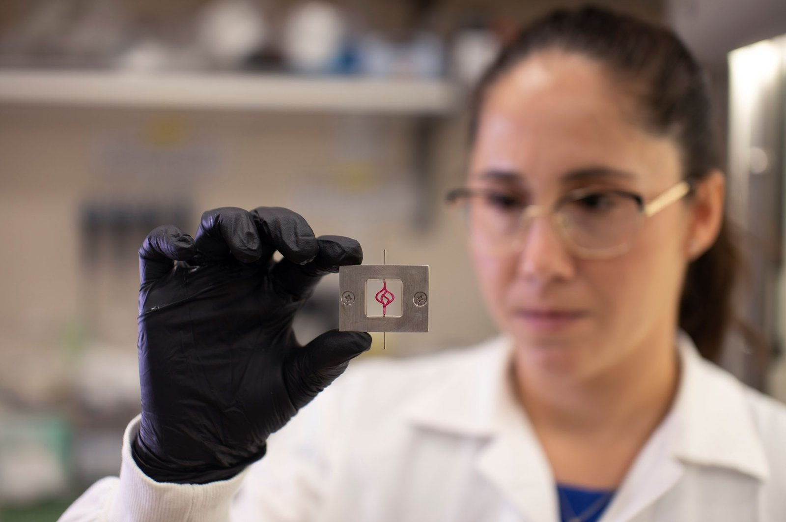 Israeli researcher Lena Neufeld examines a 3D model of a blood vessel-like tube, as part of brain cancer research that uses patients' cells to make 3D printed models of tumors, at Tel Aviv University, Israel, Aug. 17, 2021. (Reuters Photo)