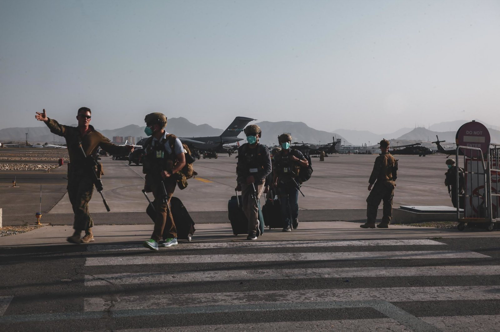 A U.S. Marine assigned to the 24th Marine Expeditionary Unit escorts U.S. State Department personnel to be processed for evacuation at Hamid Karzai International Airport, Kabul, Afghanistan, Aug. 15, 2021. (U.S. Marine Corps via AP)