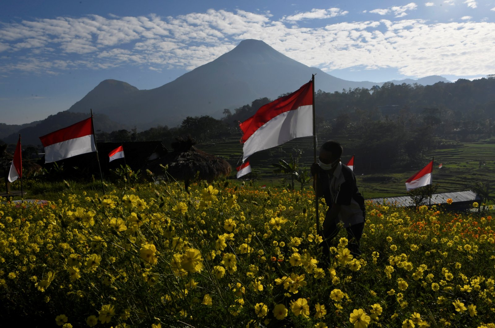 A man wearing a protective face mask holds an Indonesian flag to celebrate the country's 76th Independence Day at Refugia Park in Mojokerto, East Java province, Indonesia Aug. 17, 2021. (Reuters Photo)