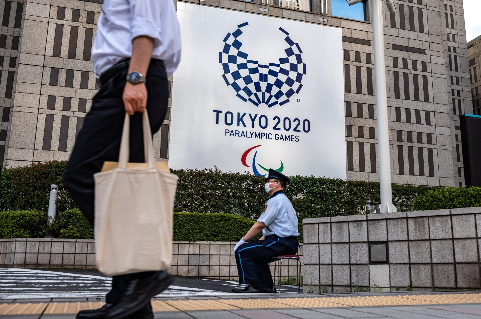 A pedestrian walks past as a security guard sits in front of a Tokyo 2020 Paralympic Games banner at the entrance to the Metropolitan Government Building, Tokyo, Japan, Aug. 19, 2021. (AFP Photo)