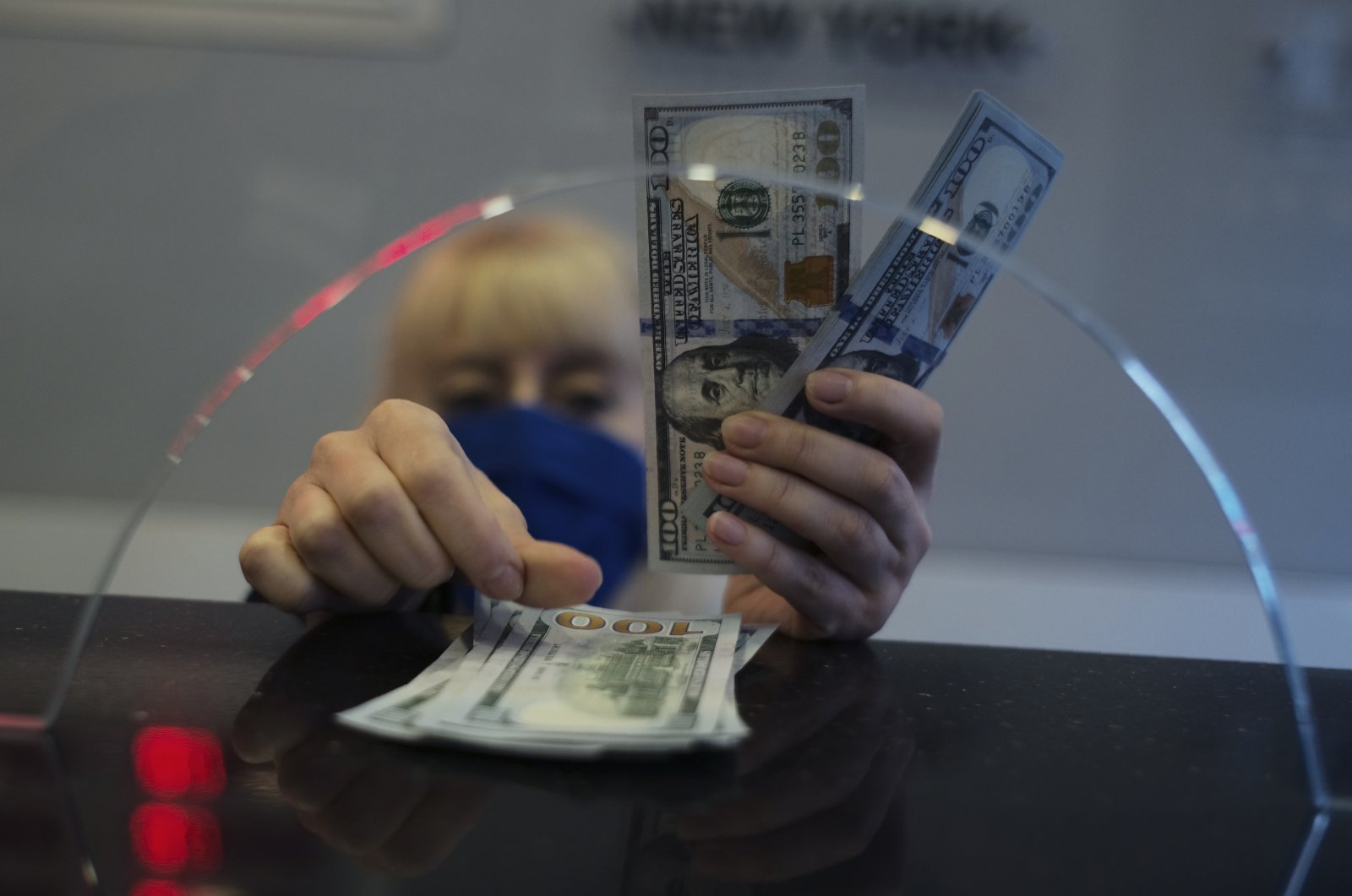 A woman counts U.S. dollar banknotes inside a currency exchange shop, in Ankara, Turkey, March 22, 2021. (AP Photo)