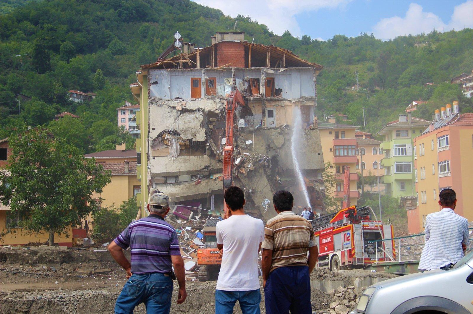 Residents watch the demolition of their building damaged in the floods, in Bozkurt, in Kastamonu, northern Turkey, Aug. 19, 2021. (IHA Photo)