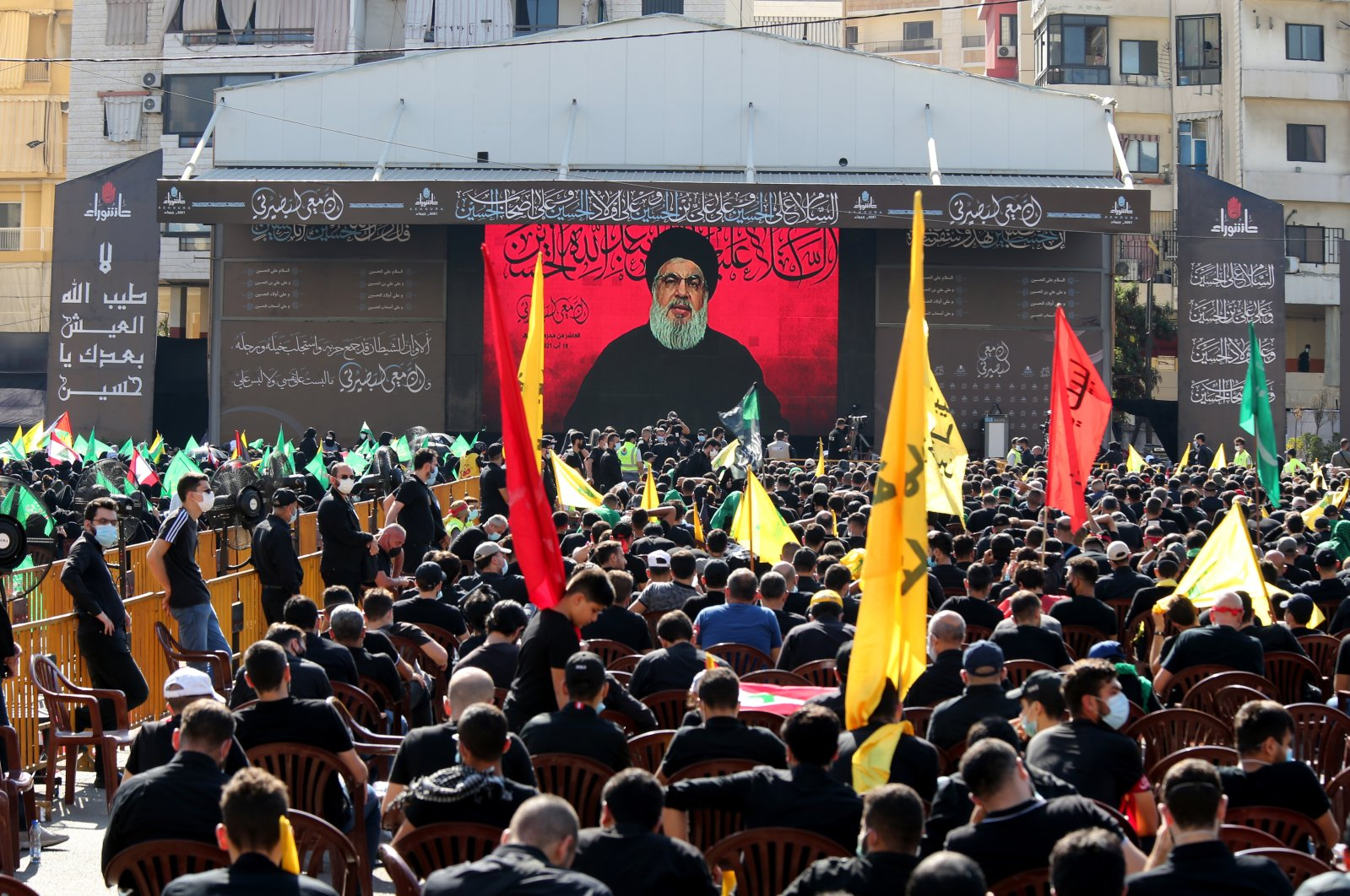 Supporters listen to the speech of Hezbollah leader Hassan Nasrallah during an Ashura Day procession in a southern suburb of Beirut, Lebanon, 19 Aug. 2021. (EPA/NABIL MOUNZER)