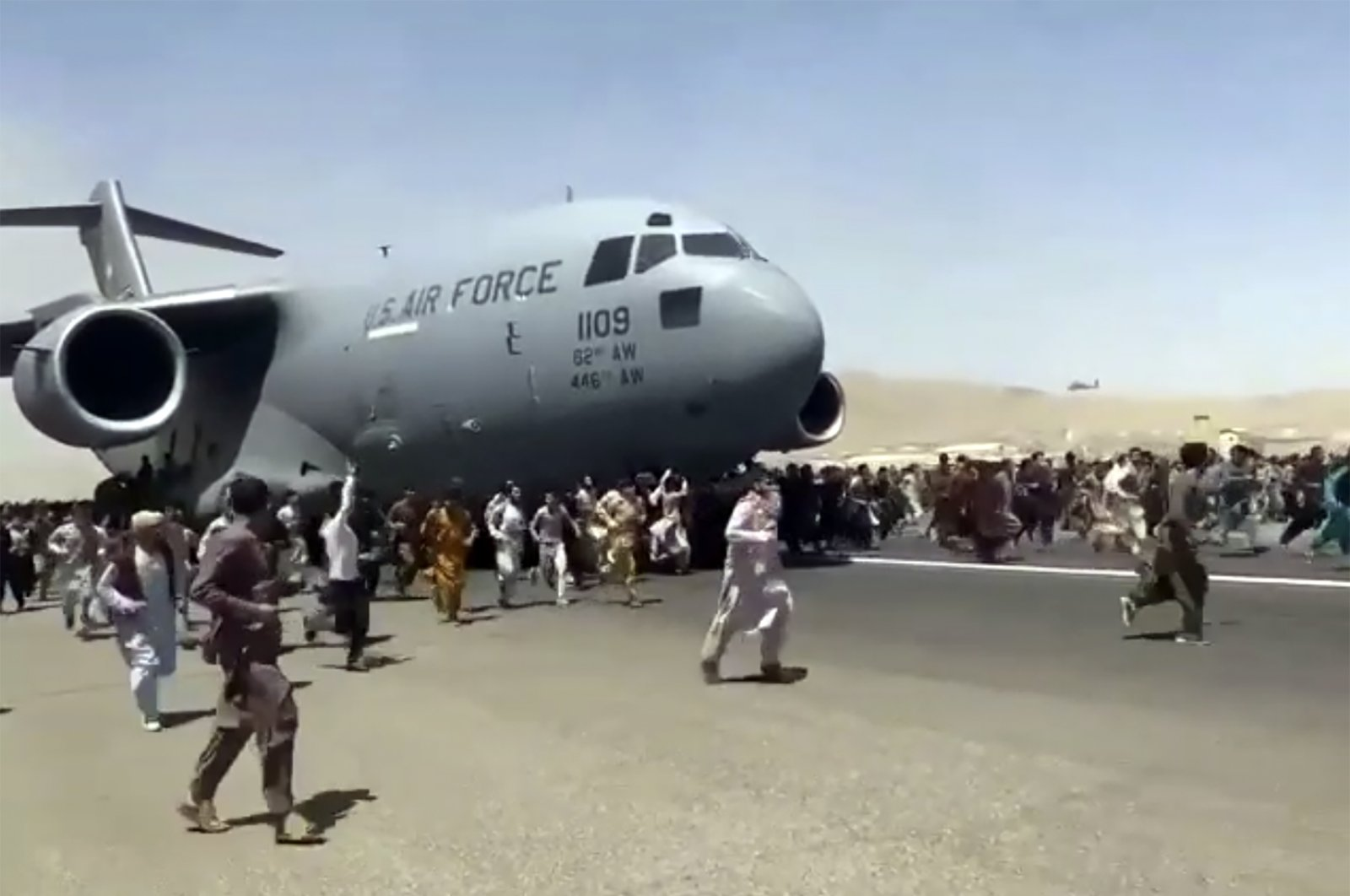 In this Aug. 16, 2021 file photo, hundreds of people run alongside a U.S. Air Force C-17 transport plane as it moves down a runway of the international airport in Kabul, Afghanistan. (Verified UGC via AP, File)