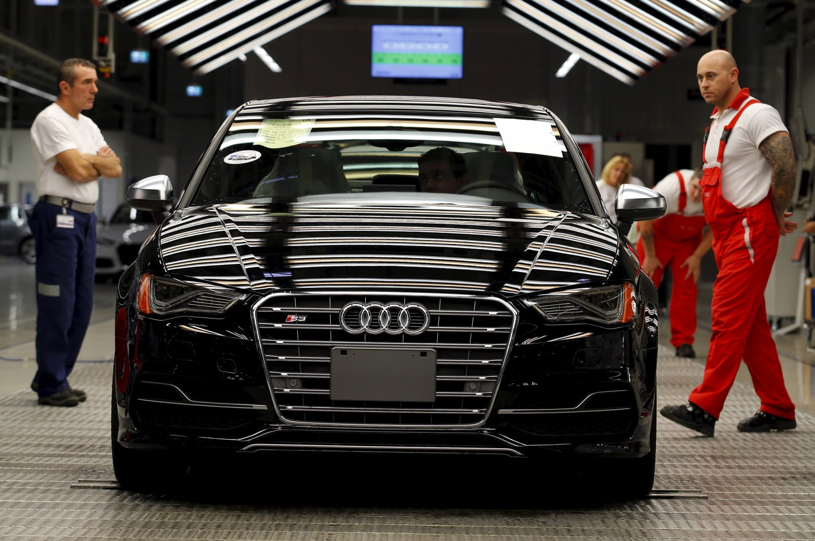 Worker stand next to a car on the assembly line as serial production of the new Audi TT roadster starts at the Audi plant in Gyor, west of Budapest, Hungary, Nov. 5, 2014. (Reuters Photo)