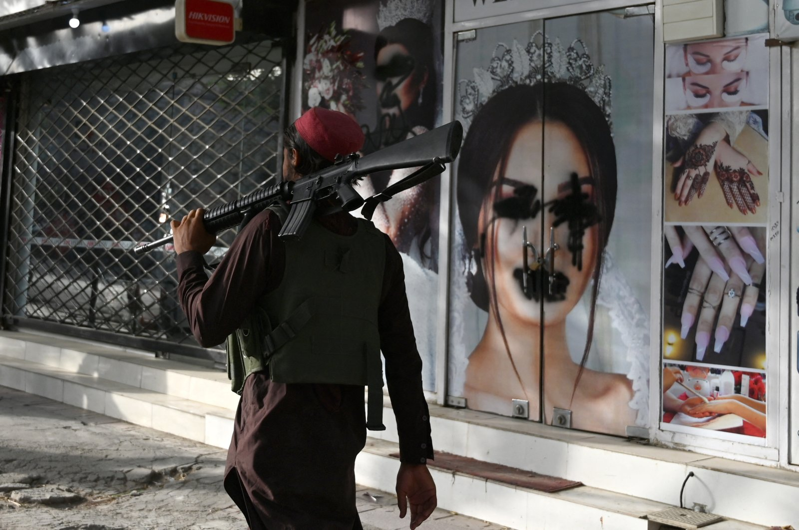 A Taliban fighter walks past a beauty salon with images of women defaced using spray paint in Shar-e-Naw in Kabul, Afghanistan, Aug. 18, 2021. (AFP Photo)
