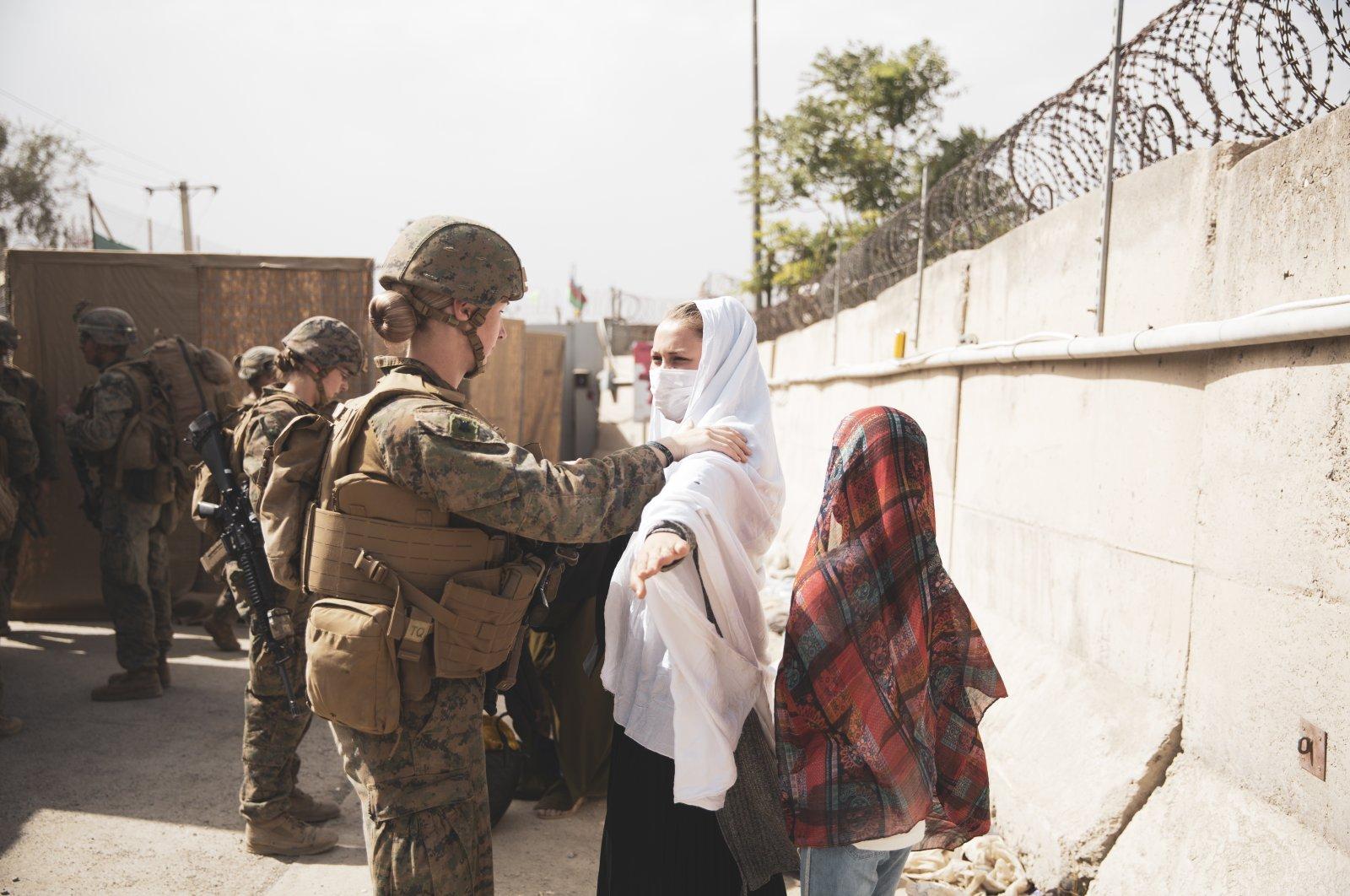 A Marine checks two civilians during processing through an Evacuee Control Checkpoint (ECC) during an evacuation at Hamid Karzai International Airport, Kabul, Afghanistan, Aug. 18, 2021. (U.S. Marine Corps photo via EPA)