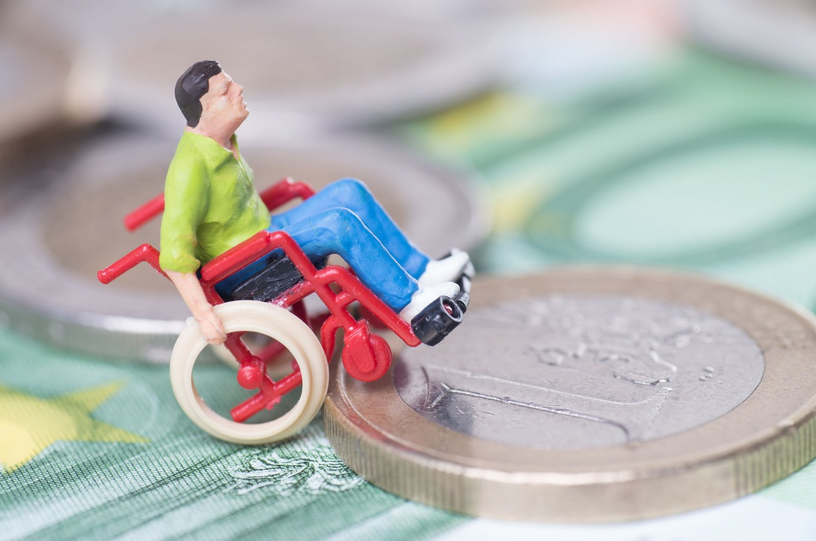 A figurine of a person in a wheelchair getting onto a coin. (Shutterstock)